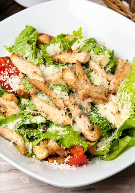 Chicken parmesan caesar salad with fresh lettuce, bread crackers and cherry tomatoes in white plate. Free Photo