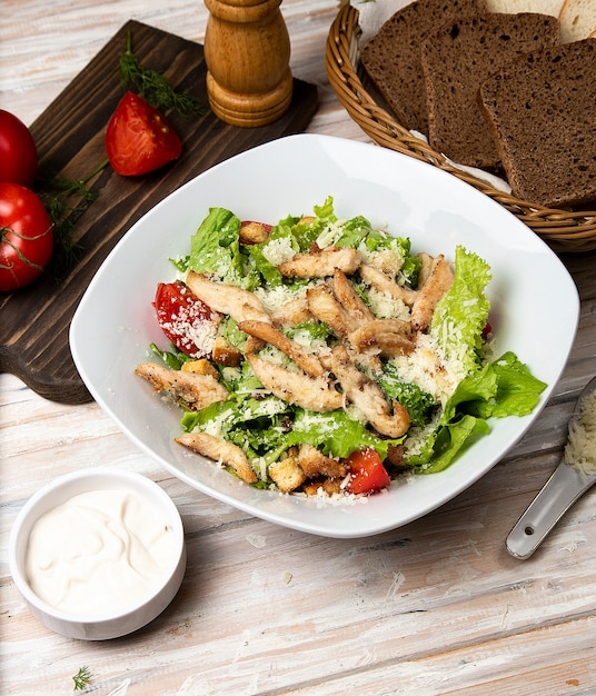 Chicken parmesan caesar salad with lettuce, cherry tomatoes inside a white bowl, served with sauce and bread. Free Photo