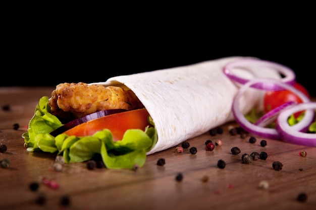 Chicken roll with lettuce tomato onion and pepper on a wooden table and black background. Premium Photo