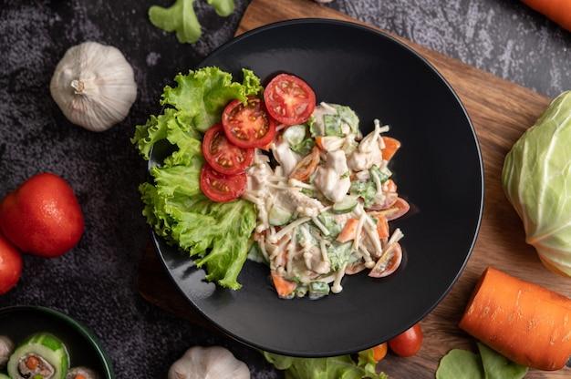 トマト、針キノコ、にんじん、レタス、きゅうりの黒いプレートのチキンサラダ 無料写真