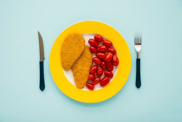 Chicken schnitzel and little tomato on yellow plate Free Photo