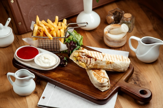 Chicken shawarmin pitwith french fries ketchup mayo and lettuce on table Free Photo