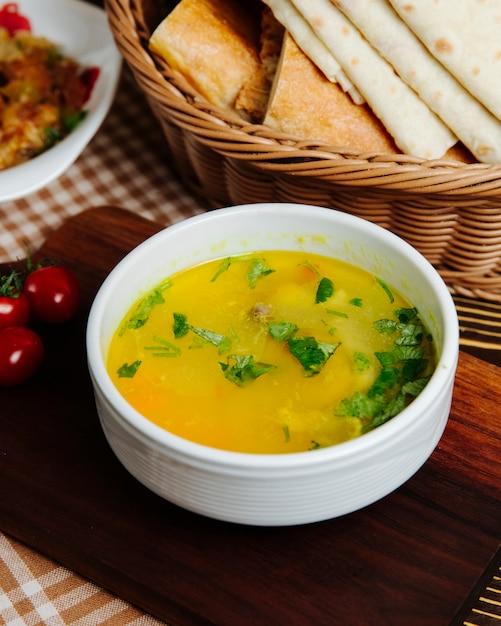 Chicken soup carrot potato greens side view Free Photo