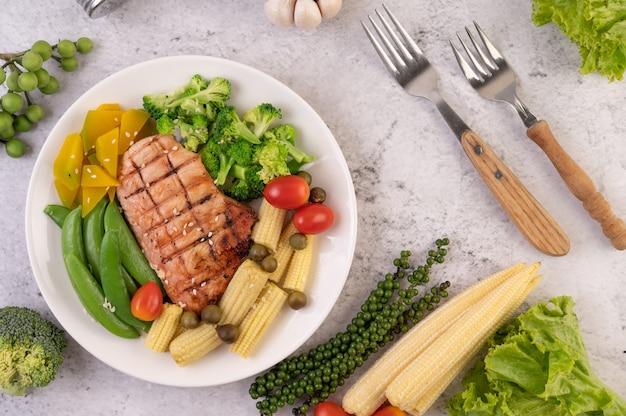 흰 접시에 흰 참깨, 완두콩, 토마토, 브로콜리, 호박을 얹은 치킨 스테이크. 무료 사진