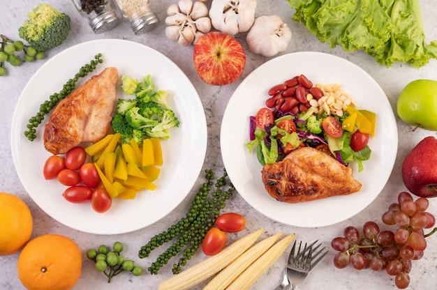 Bistecca di pollo condita con sesamo bianco, piselli, pomodori, broccoli e zucca in un piatto bianco. Foto Gratuite
