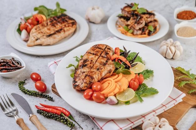 레몬, 토마토, 칠리, 당근 흰색 접시에 치킨 스테이크. 무료 사진