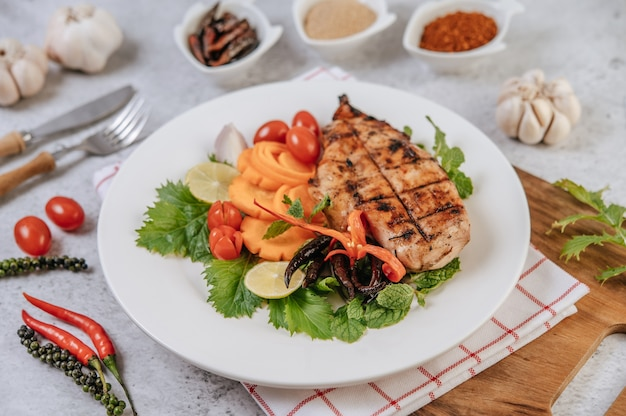 Chicken steak with lemon, tomato, chili, and carrot on white plate. Free Photo