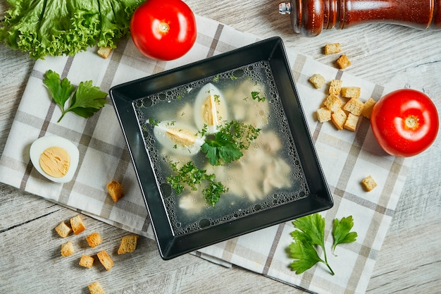 Chicken stock on a wooden table. light soup with egg, chicken meat in a composition with vegetables. top view Premium Photo