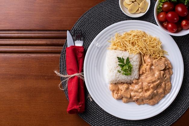 Куриный бурганов с рисом, салатом и картофельной соломкой. Premium Фотографии