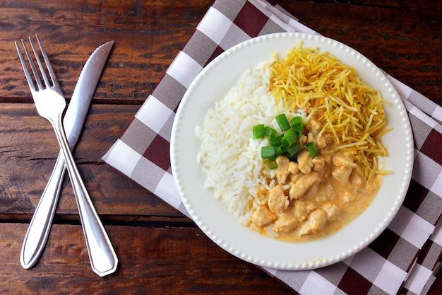 Куриный бефстроганов - это блюдо русской кухни, которое в бразилии состоит из сметаны с томатным экстрактом, рисом и картофельными чипсами. Premium Фотографии