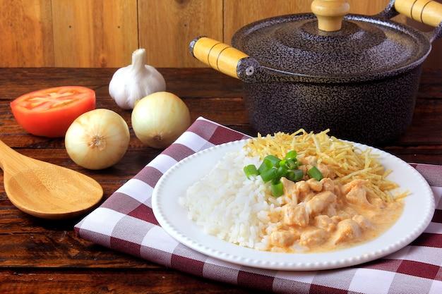 Куриный бефстроганов, сковорода и ингредиенты. в бразилии он состоит из сметаны с томатным экстрактом, рисовых и картофельных палочек на деревенском деревянном столе. Premium Фотографии