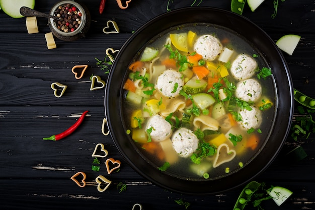 Chicken and vegetable soup with meatballs, zucchini and pasta. flat lay. top view Premium Photo