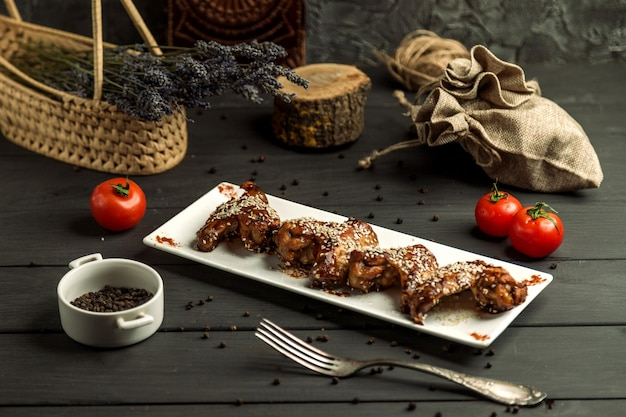 Chicken wings cooked in teriyaki sauce garnished with sesame Free Photo