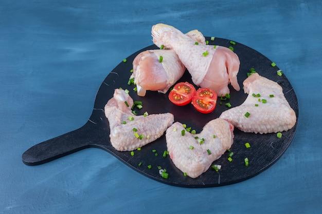 닭 날개, 도마에 나지만, 파란색 테이블에. 무료 사진