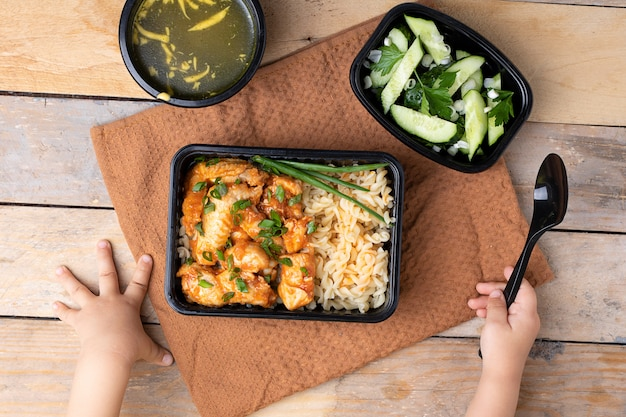 Chicken wings and rice with onion, kids hands with spoon Premium Photo