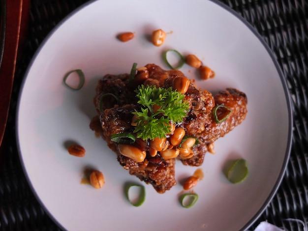 Куриные крылышки с фасолью на тарелке Premium Фотографии