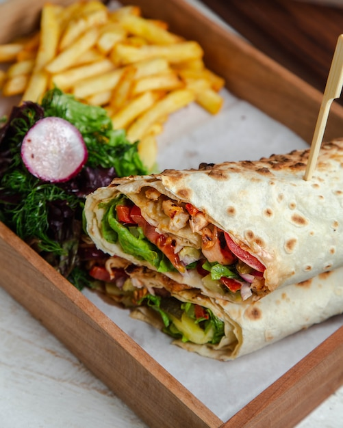 Chicken wrap with vegetables and french fries Free Photo