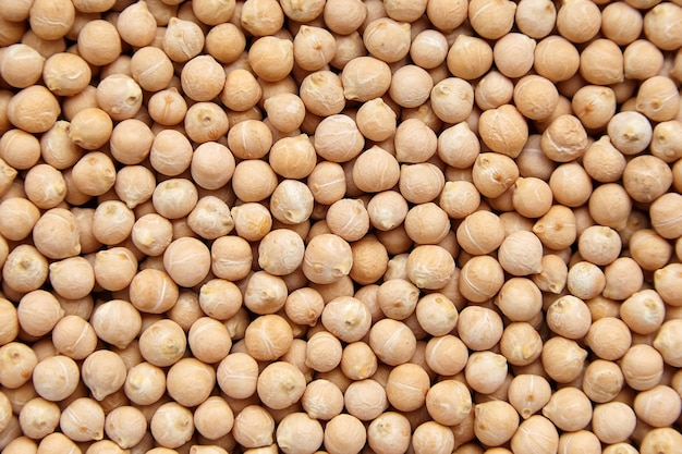 Chickpea seeds, food texture, background, top view. chick peas, or garbanzo beans, legume. protein food. closeup Premium Photo