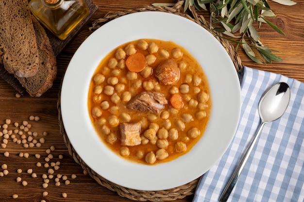 Тушеное блюдо из нута с говядиной, колбасой, беконом, морковью и оливковым маслом Premium Фотографии