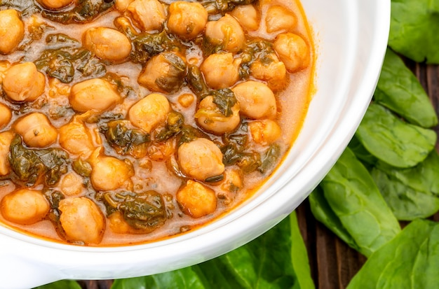 Chickpea stew with spinach (potaje). delicious spoon dish for autumn and winter. traditional food. foreground. Premium Photo