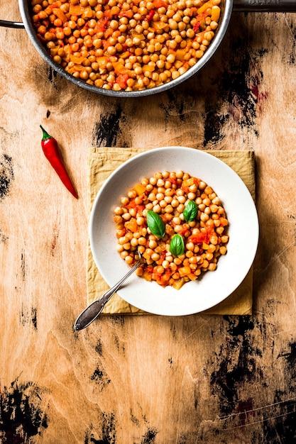 ひよこ豆のシチュー、トマト、黄ピーマン、唐辛子、バジルの葉。上面写真、木の表面。皿にスプーンで入れます。 Premium写真