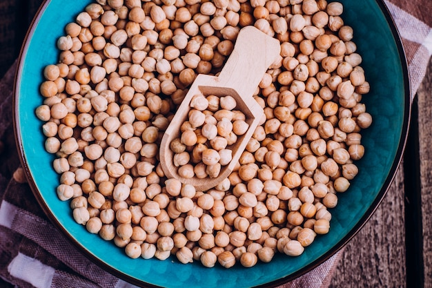 Chickpeas in bowl on tablecloth with wooden spoon on wooden table. healthy vegan food Premium Photo