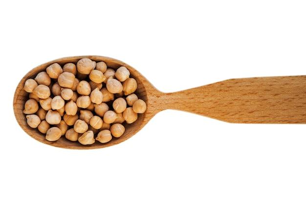 白い背景の上面図に分離された木のスプーンでひよこ豆 Premium写真