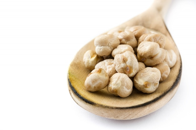 Chickpeas uncooked on wooden spoon isolated  copy space Premium Photo