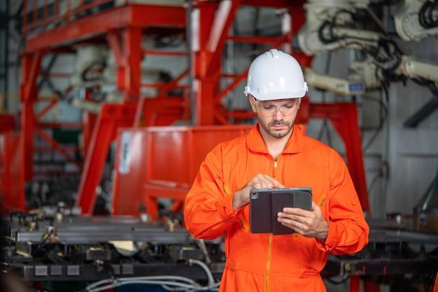 ハード帽子のチーフエンジニアは、ラップトップを握っている間、ライトモダンな工場を通り抜けます。現代の産業環境で成功したハンサムな男。 Premium写真