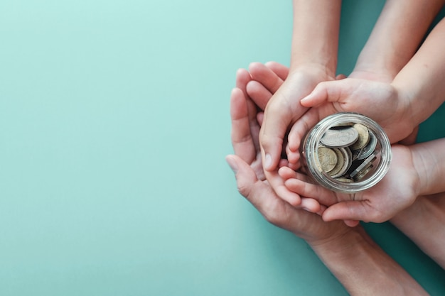 Child and adult holding money jar, donation, saving concept Premium Photo
