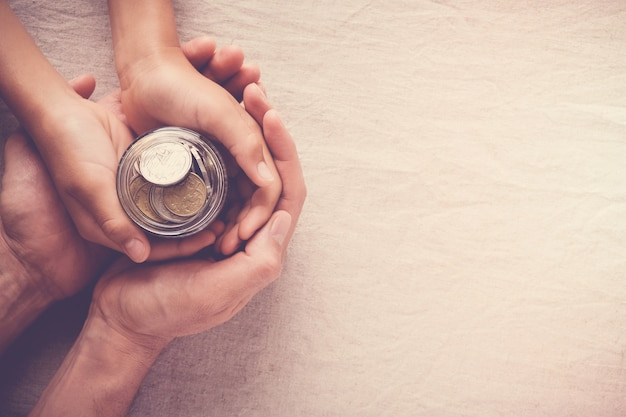Child and adult holding money jar, donation, saving concept Premium Photo