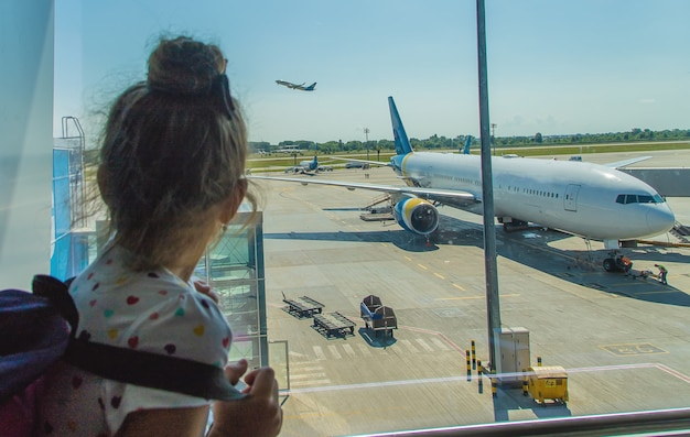 A child at the airport on the background of the aircraft Premium Photo