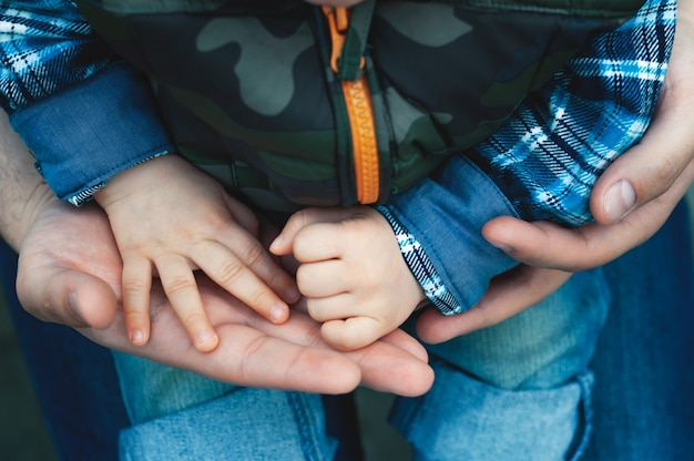 A child in the arms of his dad on the street Premium Photo