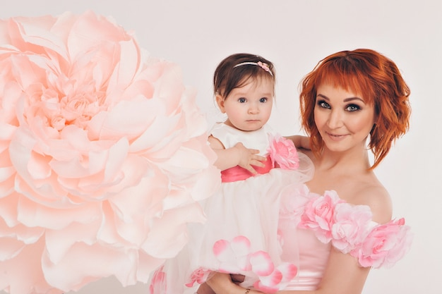 The child in the arms of his mother in a pink dress of flowers. Premium Photo