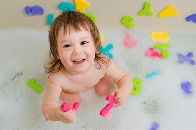 Child in a bath with foam Premium Photo