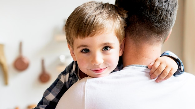 Child being held by father over the shoulder view Free Photo