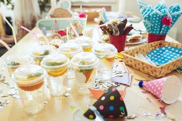 子供の誕生日の装飾。ケーキ、飲み物、パーティーガジェットを上から見たピンクのテーブルセッティング。 無料写真