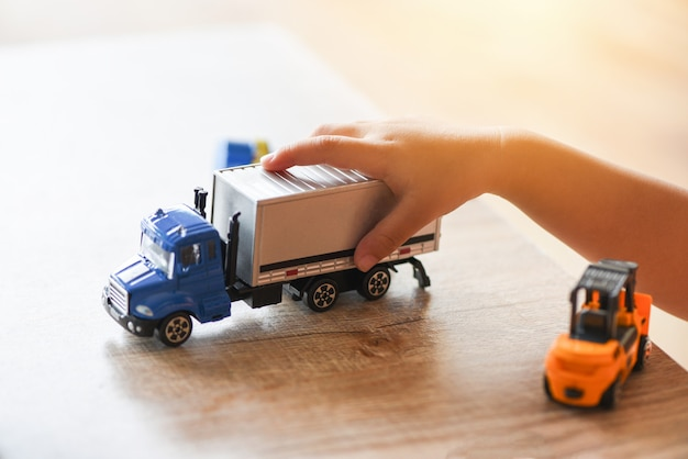 Child boy playing toys on table at home - kid hands playing toy car truck Premium Photo
