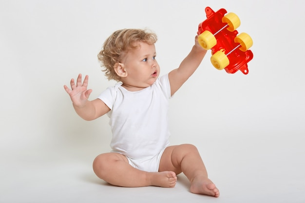 Child boy playing with toys indoors, sitting on floor and raising hands up, holding red and yellow toy car, looking at it with big eyes Premium Photo