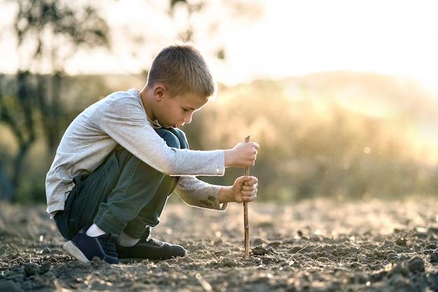 屋外の黒い土の地面を掘って木の棒で遊ぶ子供男の子。 Premium写真