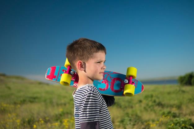 Child boy with skateboard in nature Premium Photo