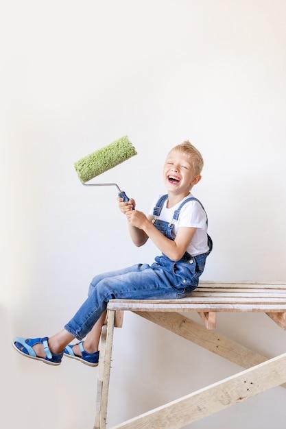 Ребенок строитель сидит на строительной лестнице в квартире и держит сруб для покраски стен Premium Фотографии