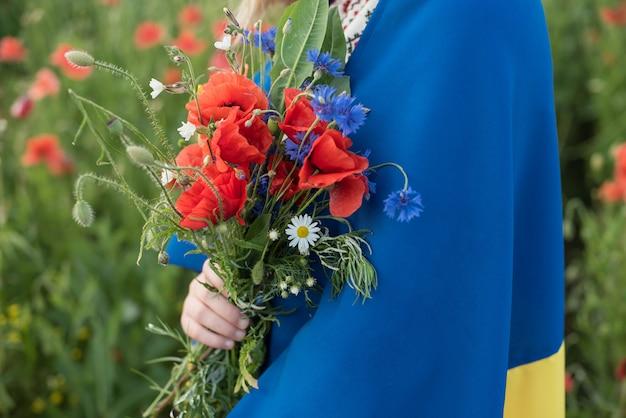 Ребенок несет развевающиеся синий и желтый флаг украины в маковое поле. день независимости украины. день флага. Premium Фотографии