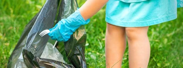 Ребенок собирает пластиковый мусор с травы, выбрасывая мусор в мешок для мусора в парке Premium Фотографии