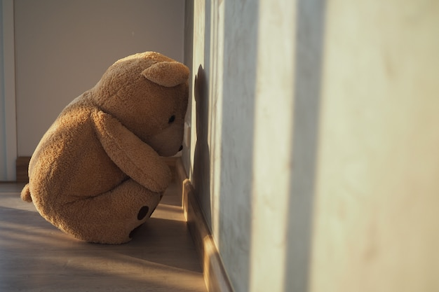 Child concept of sorrow teddy bear sitting leaning against the wall of the house alone, look sad and disappointed Premium Photo