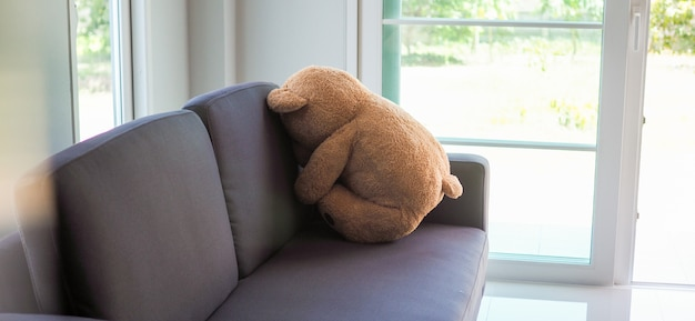 Child concept of sorrow. teddy bear sitting leaning against the wall of the house alone, look sad and disappointed. Premium Photo