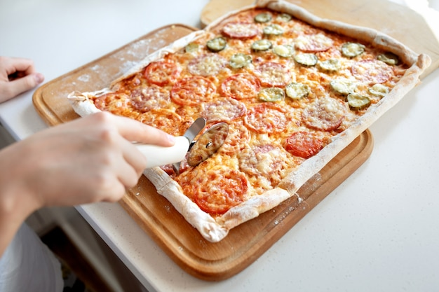 Child cuts pizza with a roller cutter close up Premium Photo
