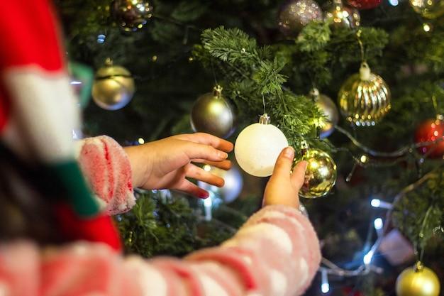 아름다운 크리스마스 트리를 장식하는 아이 무료 사진