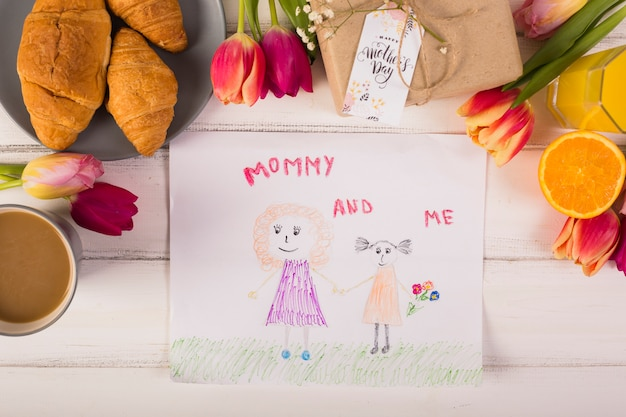 Child drawing around classic breakfast with flowers Free Photo