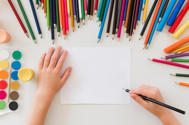 Child drawing with colorful pencils Premium Photo